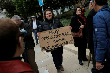 A woman holds a sign during a demonstration demanding higher state pensions, in Malaga