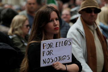"""A woman holds a sign that reads """"For them for us"""" during a demonstration demanding higher state pensions, in Malaga"""