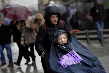 """A woman holds a placard reading """"Do not laugh more about us, Rajoy"""" during a demonstration demanding higher state pensions in Gijon"""