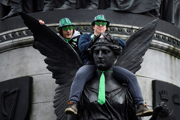People sit on a statue to watch the St. Patrick's Day parade in Dublin