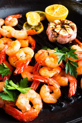 Prawns roasted on grill frying pan with lemon and garlic. Grilled shrimps, prawns. Seafood. Closeup. Dark background