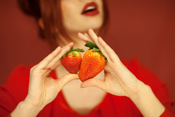 Beautiful woman hands holding some strawberries in her hands, sensual studio shot can be used as background