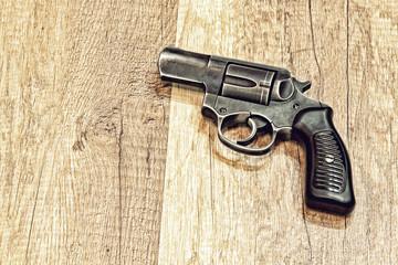 Short-barreled revolver gun on wooden backround.