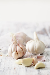 Peeled cloves of garlic and a head of garlic on old wooden table