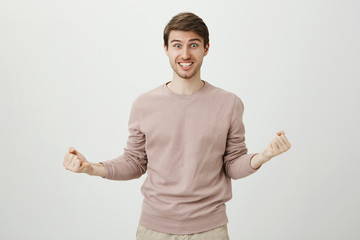 Portrait of playful positive caucasian good-looking man with bristle squeezing fists while being excited and saying yes, celebrating victory or success, standing over gray background.