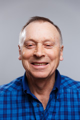 Portrait of a smiling elderly man on a gray background