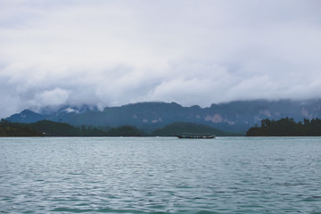 Boat in the distance in a tropical coast in a rainy day