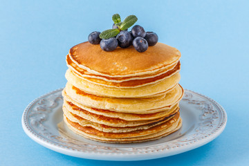 Pancakes with berries on a bright pastel background