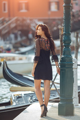 Travel tourist girl on vacation walking happy by Grand Canal. Attractive young romantic woman standing on the pier against beautiful view on venetian chanal with boats and gondolas in Venice, Italy