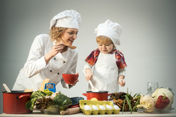 Chef and assistant near kitchen equipment and food products