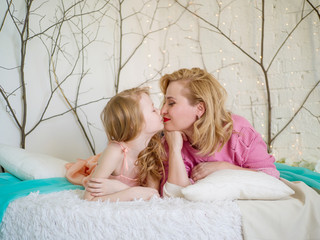 Mom and daughter kiss on the bed indoors