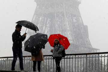People walk on a bridge near the Eiffel Tower during heavy snowfall in Paris