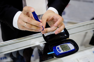 Man pricking a finger for measuring glucose level in his blood drop by using digital glucometer