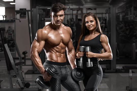 Sporty sexy couple showing muscle and workout in gym. Muscular man and woman