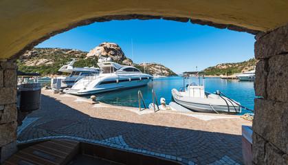 Luxury yachts seen from an arch in Poltu Quatu