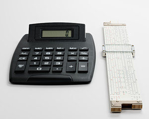 Large black calculator and a white slide rulers both used for calculating numbers