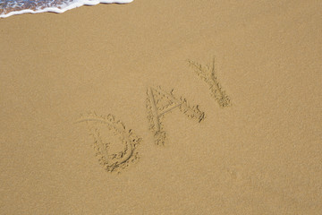 Day written in the sand on sea background