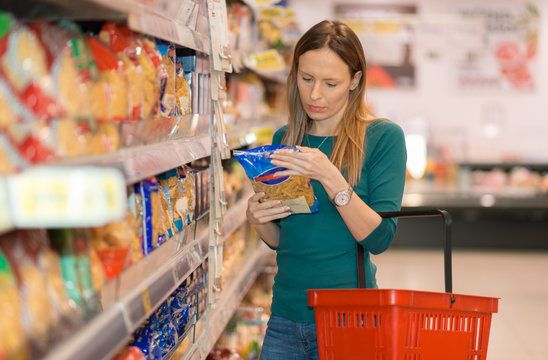 Woman doing shopping of pasta in the mega market