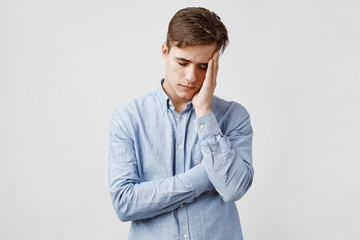 Picture of exhausted young man in blue casual shirt. Guy worked all night to send his project in time. How to survive morning at university when you did not sleep at all.
