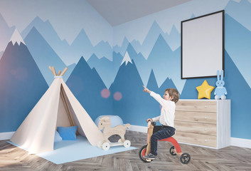 Cute boy on a tricycle in his nursery