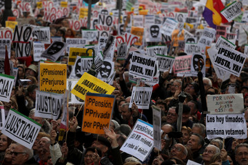 People hold placards as they take part in a demonstration demanding higher state pensions, in Madrid