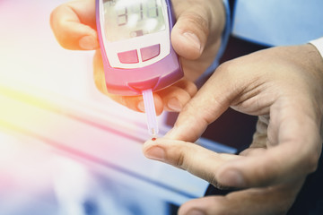 Glucometer - medical device. Man checks blood sugar level test by blood from finger, diabetic disease, insulin protection