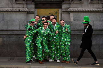 People wearing Shamrock suits queue for an ATM on St. Patrick's Day in Dublin