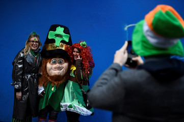 Man takes a picture of people dressed as leprechauns on St. Patrick's Day in Dublin