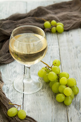 white wine in a glass with a bunch of green grapes against wooden background