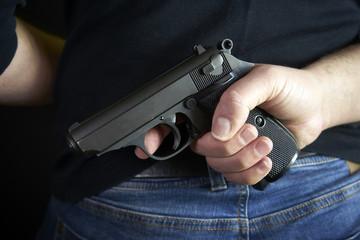 Terrorist thief man holding short gun in his hand. Hidden gun on back side body.