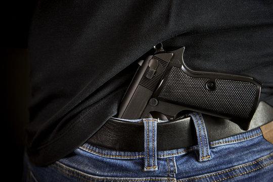 Hidden gun back side to man in blue jeans