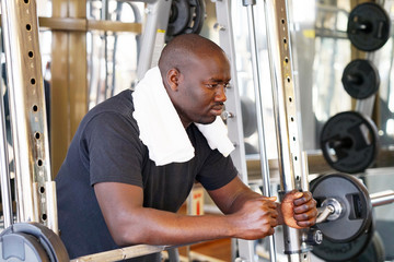 African man is concentrated on a power exercise with a barbell in the gym. A man resting after exercise with weight. The concept of health and strength.