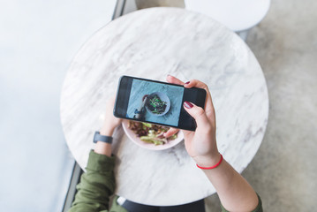 A woman makes a photo of her food at the restaurant at the table. The blogger picks up a salad at the table.