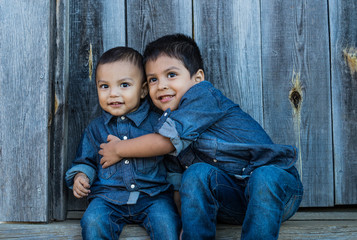 two latino children sitting on a stair case