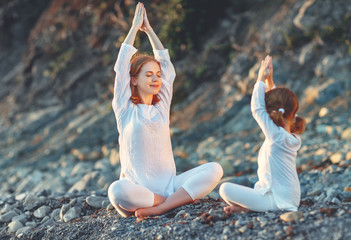 Fototapete - Happy family mother and child doing yoga, meditate in lotus position on beach