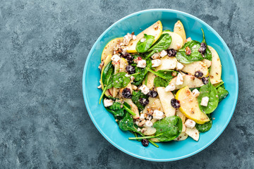 salad bowl of spinach, apple, white cheese, nuts and cranberry. top view, healthy diet eating, superfood, space for a text
