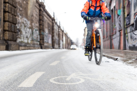 A snow-capped bike path and a partial view of a cyclist