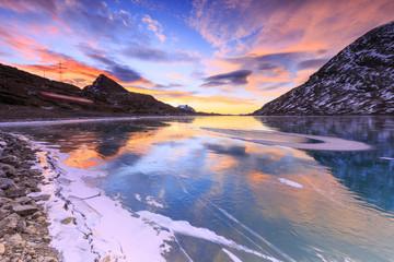 Scenic view of frozen Lago Bianco lake during sunrise