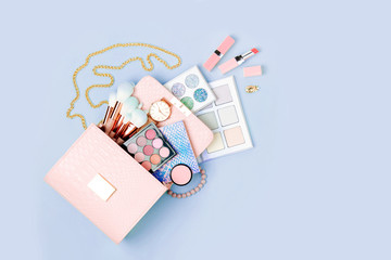 Wall Mural - Cosmetic products flowing from Makeup bag on pastel blue background.  Flat lay, top view. Fashion concept