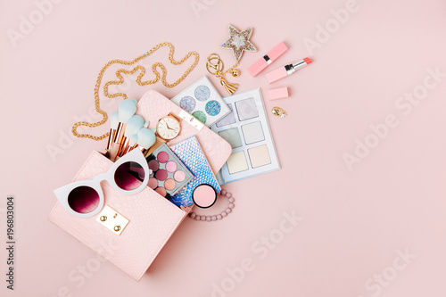 cosmetic products flowing from makeup bag on pastel pink background