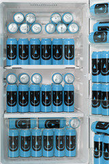 The open fridge is full of colored cans with a drink. Stock of beer in the refrigerator at home. A fridge filled with cans of beer with a funny image.