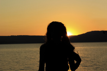 Girl silhouette in sunset time near sea with beautiful nature mountain landscape and orange colors