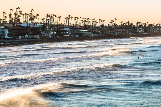 Surfers at dawn amid crashing waves in Oceanside, California, located in San Diego County.