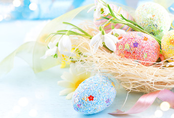 Fotoväggar - Easter colorful eggs background. Beautiful colorful eggs with decorations over blue wooden background, border design in pastel colors. Spring flowers, holiday ribbon and painter eggs in the nest