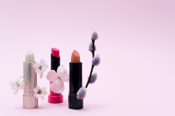 Female wallpaper with cosmetics. Different colored lipsticks decorative of flowers in line. Beauty frame background.