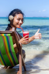 Ethnic girl with a white flower in her hair relaxed by the sea with red juice and shows gesture thumb up. Beautiful woman sitting in a deck chair on the sea beach. Tropical holidays on island.