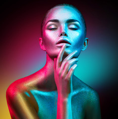 Wall Mural - Fashion model woman in colorful bright sparkles and neon lights posing in studio, portrait of beautiful sexy girl. Art design colorful vivid makeup
