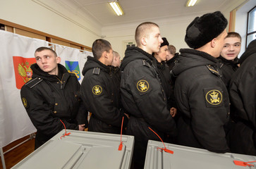 Sailors queue to vote during the presidential election at a polling station in the far eastern city of Vladivostok