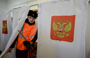 A sailor holds his ballot as he leaves a voting cabin during the presidential election at a polling station in the far eastern city of Vladivostok