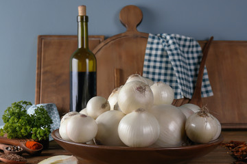 Bowl with fresh white onions and spices on wooden table